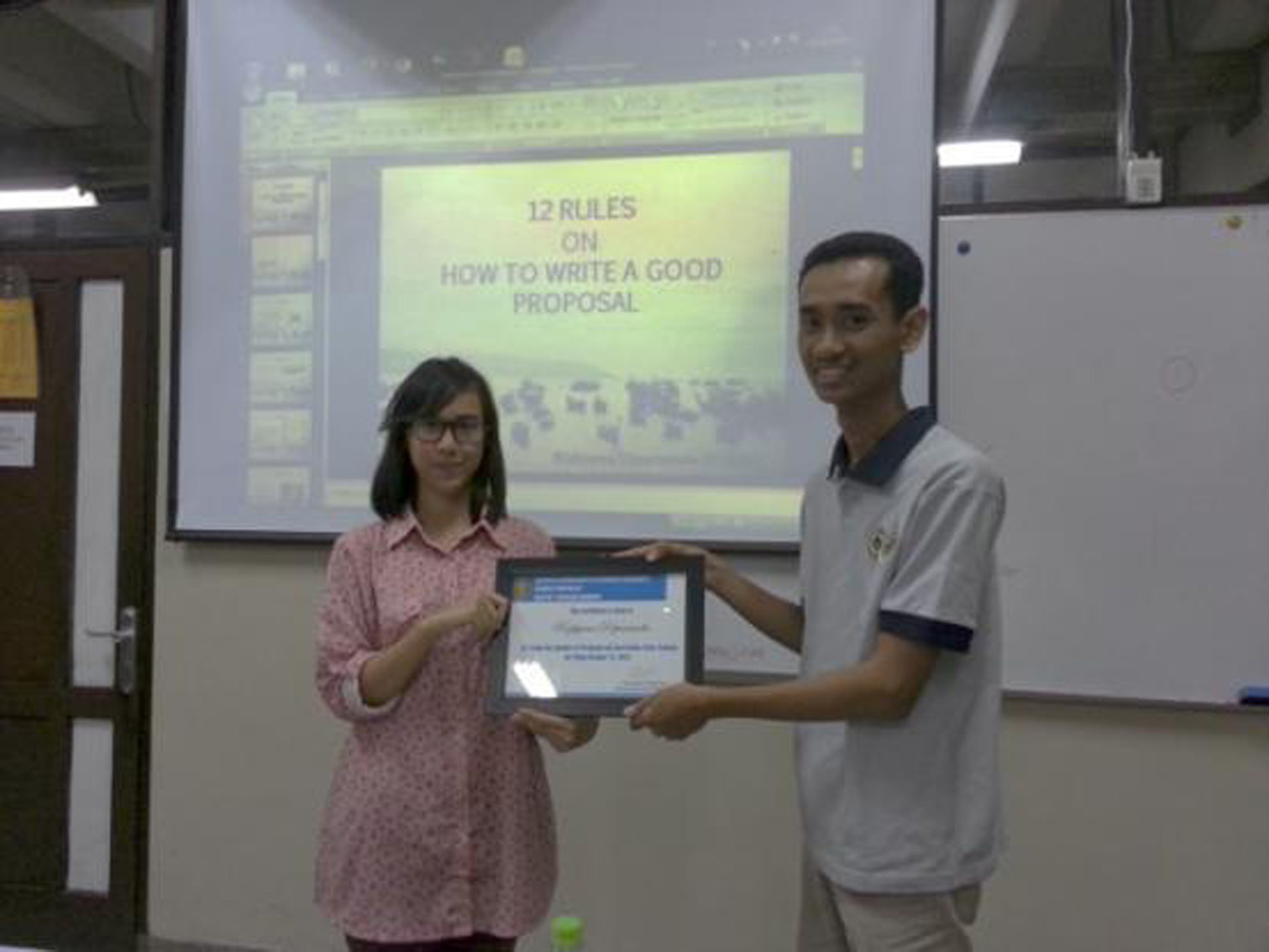 RizkyanaDipananda (left) was given a certificate from IwanSetiawan as the project officer (right).